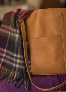 Close up of tan leather bag and plaid scarf